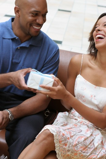 Young man giving a gift to a young woman : Stock Photo