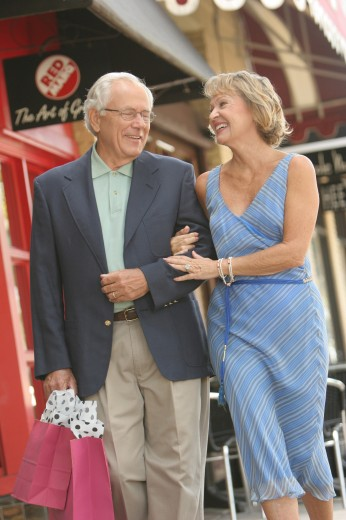 Senior couple walking with shopping bags : Stock Photo