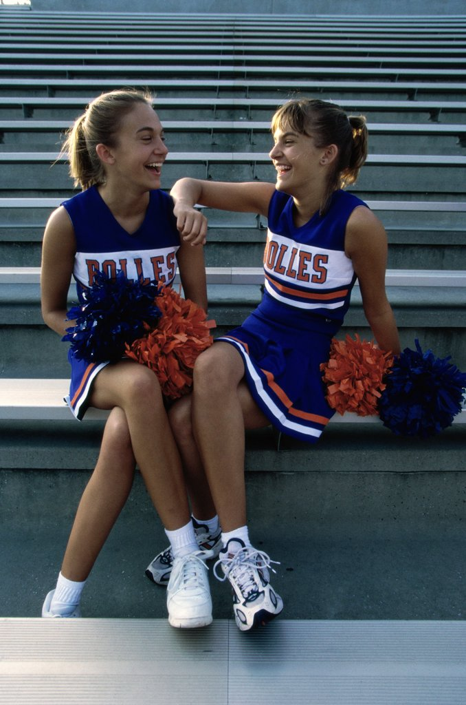 Two cheerleaders sitting with pom-poms : Stock Photo