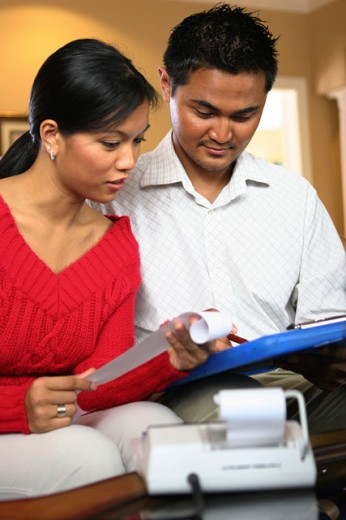 Stock Photo: 1574R-017858 Young couple looking at a file