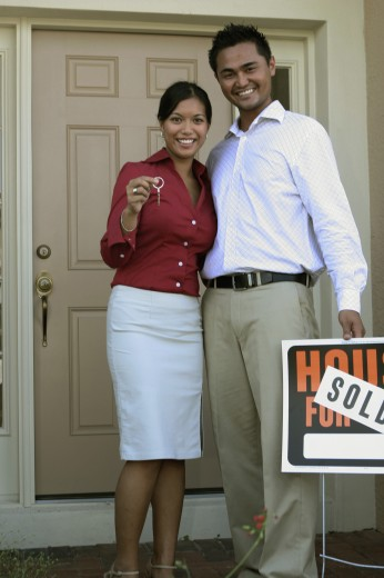 Portrait of a young couple standing outside a house holding a sold sign : Stock Photo