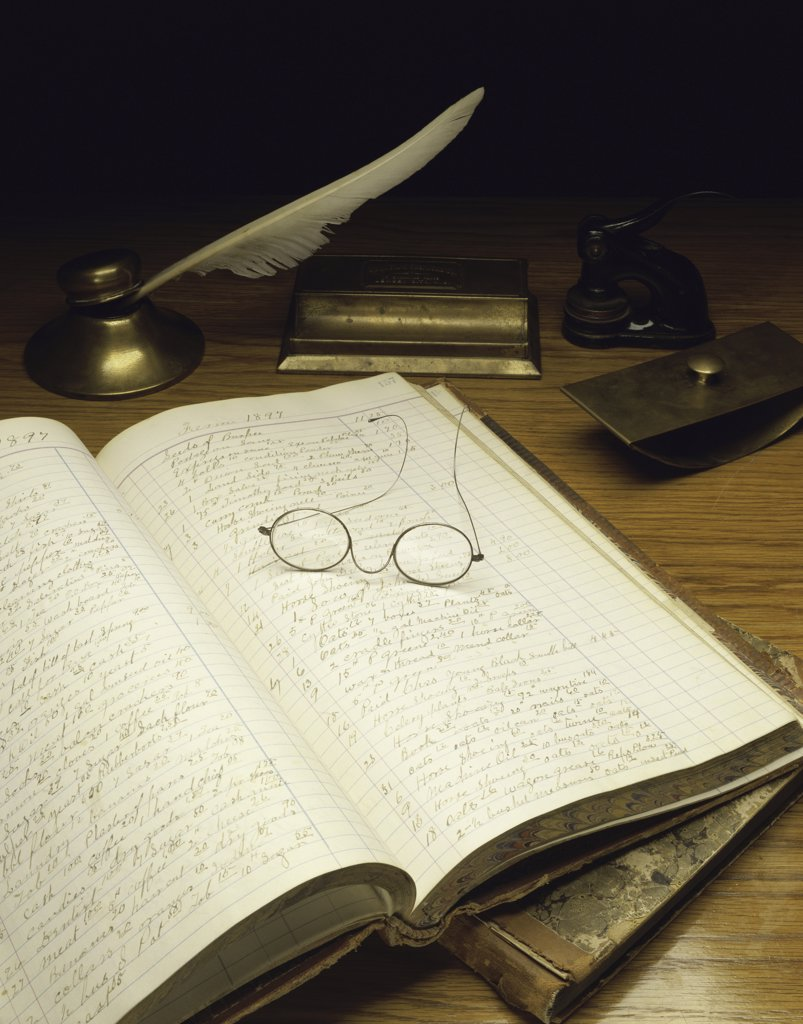 Close-up of an accounting ledger with eyeglasses and a quill pen, USA : Stock Photo