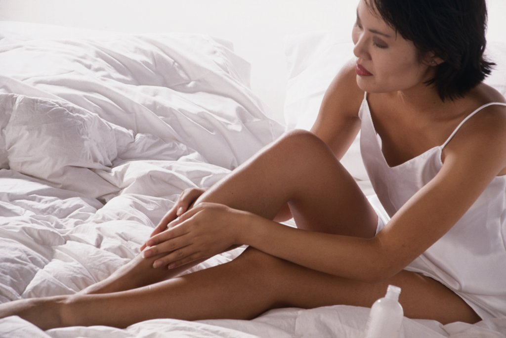 Young woman sitting on a bed and rubbing her leg : Stock Photo