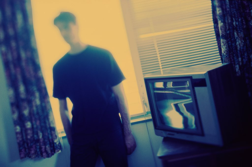Young man standing beside a television : Stock Photo