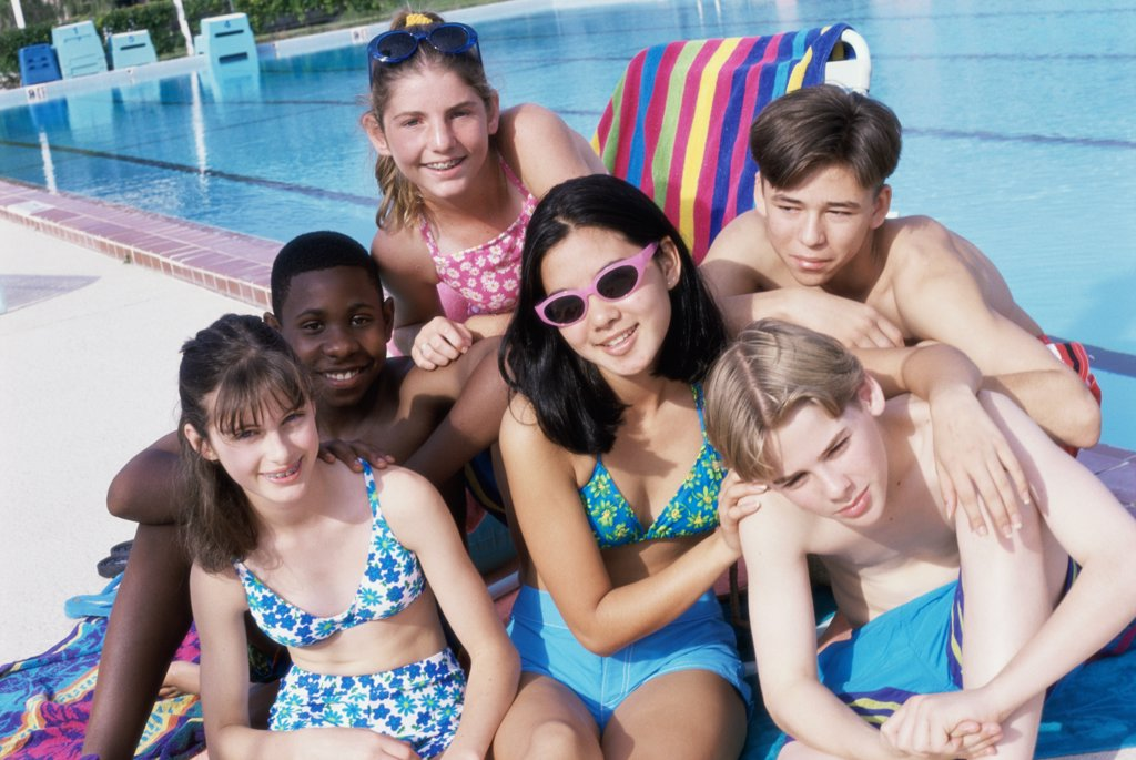 Portrait of a group of teenagers sitting beside a swimming pool : Stock Photo
