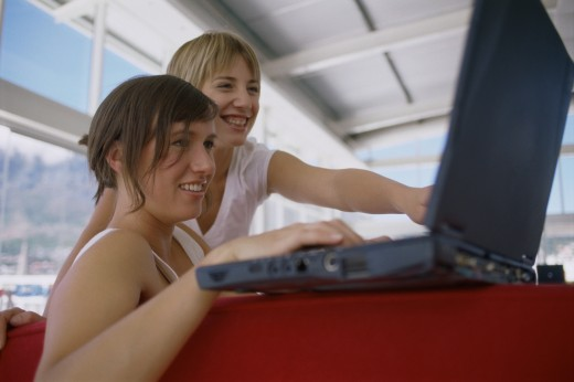 Close-up of two young women looking at a laptop smiling : Stock Photo