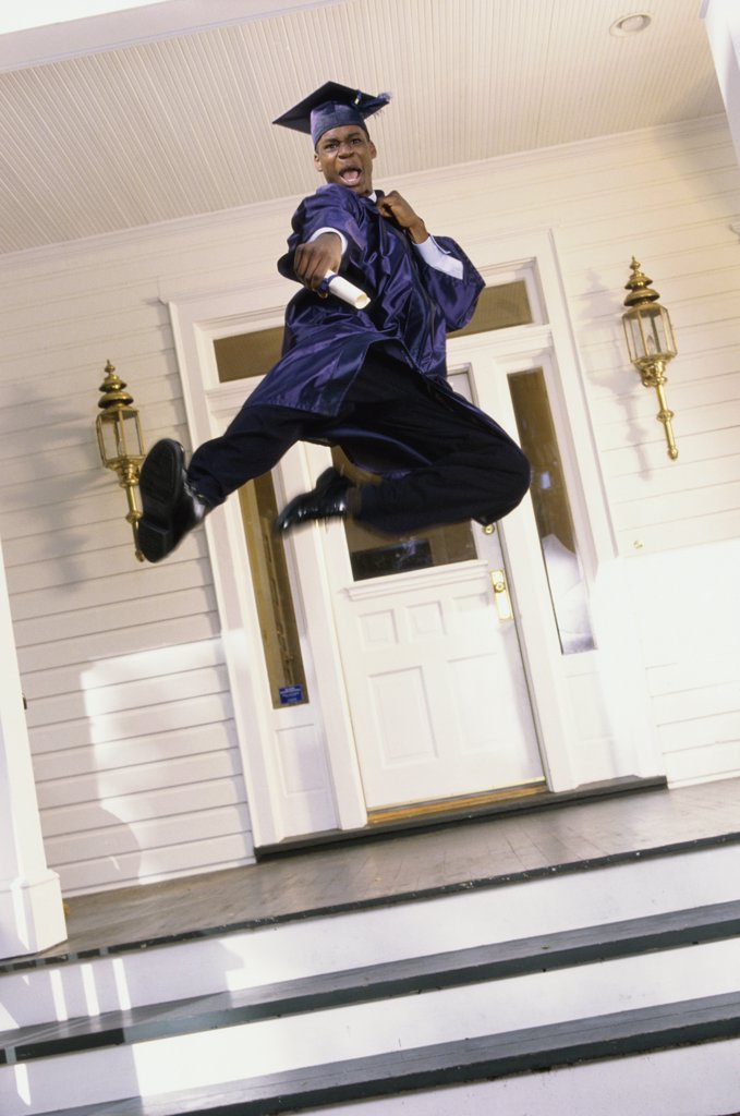 Teenage boy in a graduation outfit leaping on the porch : Stock Photo