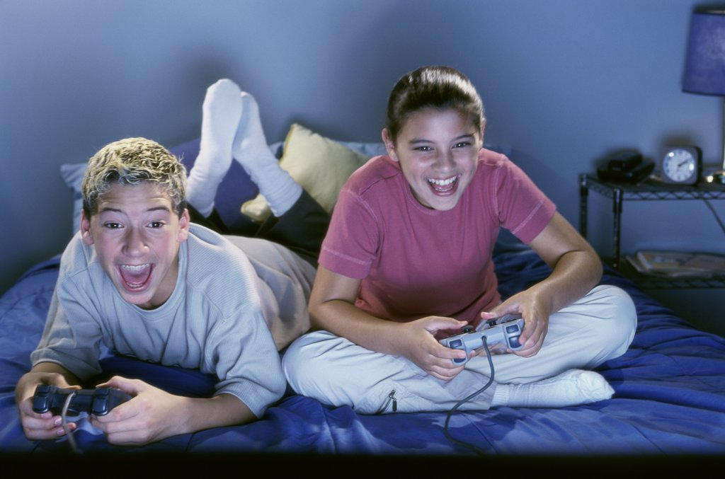 Stock Photo: 1574R-01994J Teenage boy and girl sitting on the bed and playing a video game