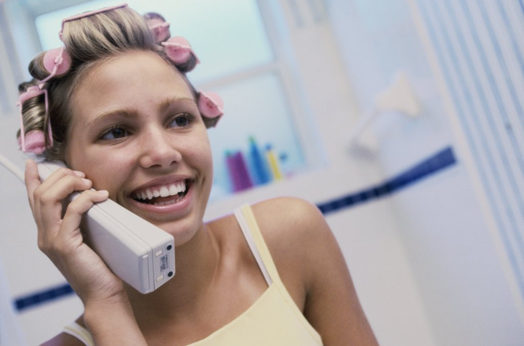 Young woman with curlers in her hair talking on a telephone : Stock Photo