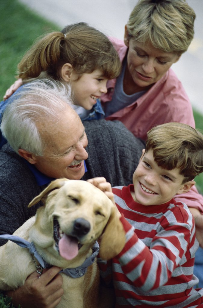 Grandparents with their grandson and granddaughter holding their dog : Stock Photo