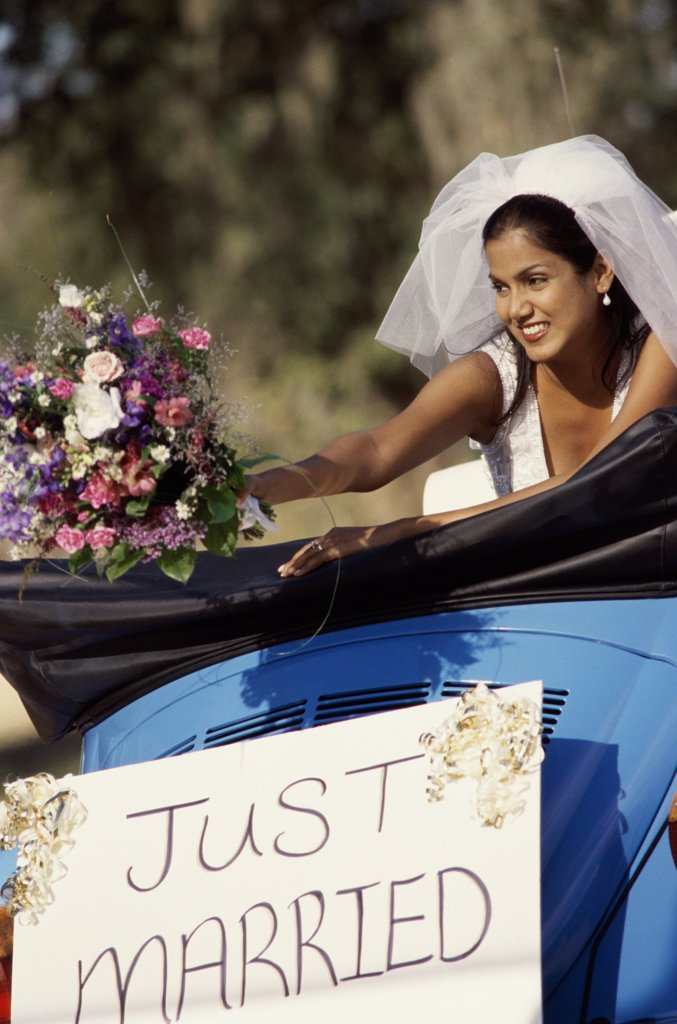 Bride preparing to toss a bouquet of flowers from a convertible car : Stock Photo