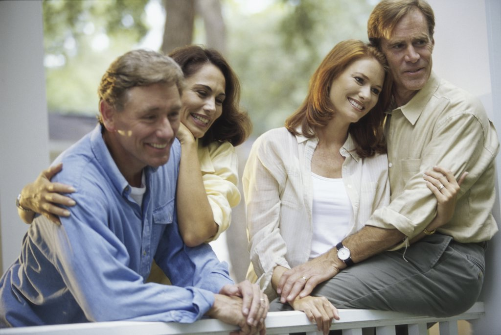 Two mid adult couples sitting together : Stock Photo