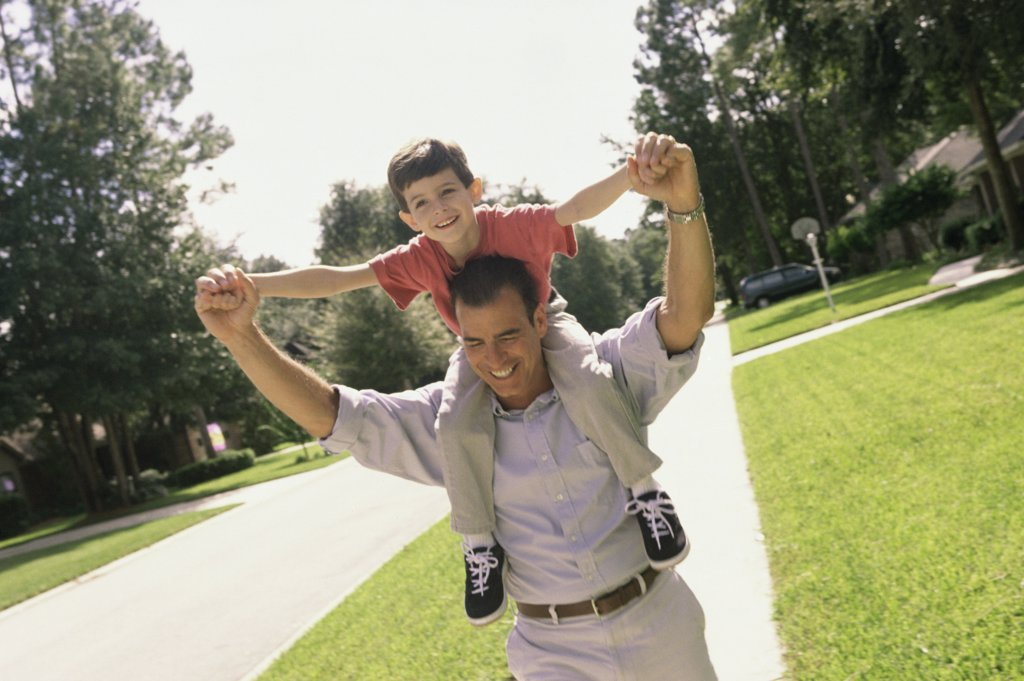 Stock Photo: 1574R-02183A Father carrying his son on his shoulders