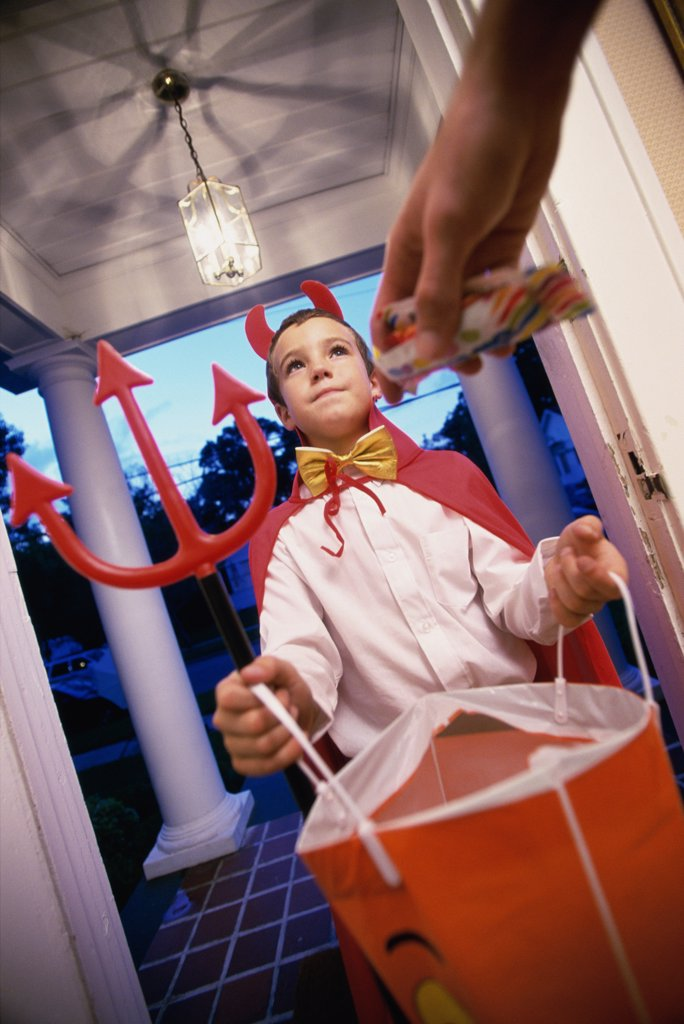Low angle view of a boy dressed as the devil on Halloween : Stock Photo