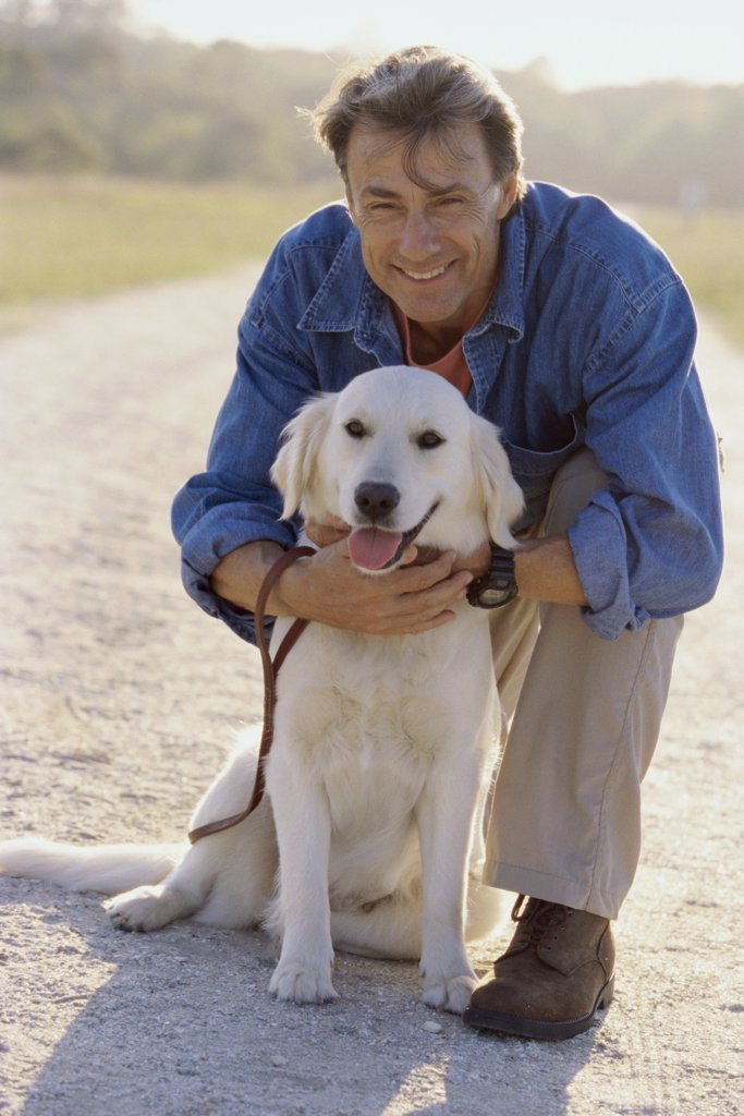 Portrait of a mature man holding his dog : Stock Photo