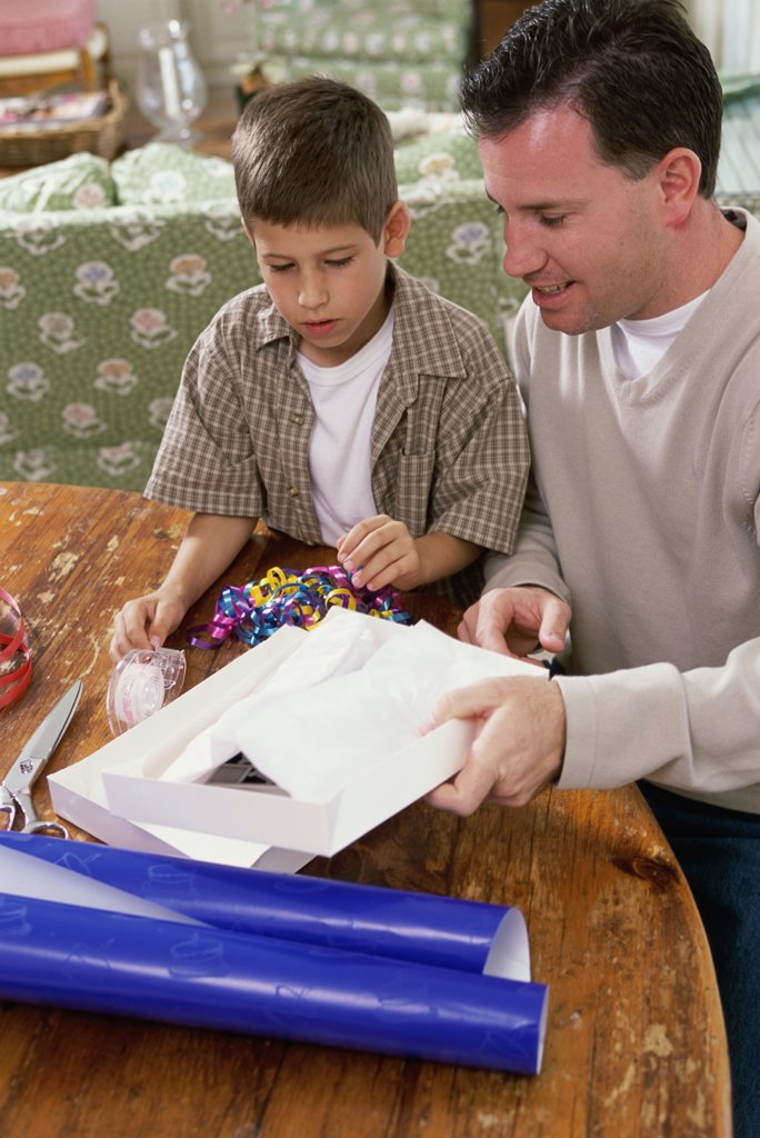 Stock Photo: 1574R-02359A Father and son wrapping a gift