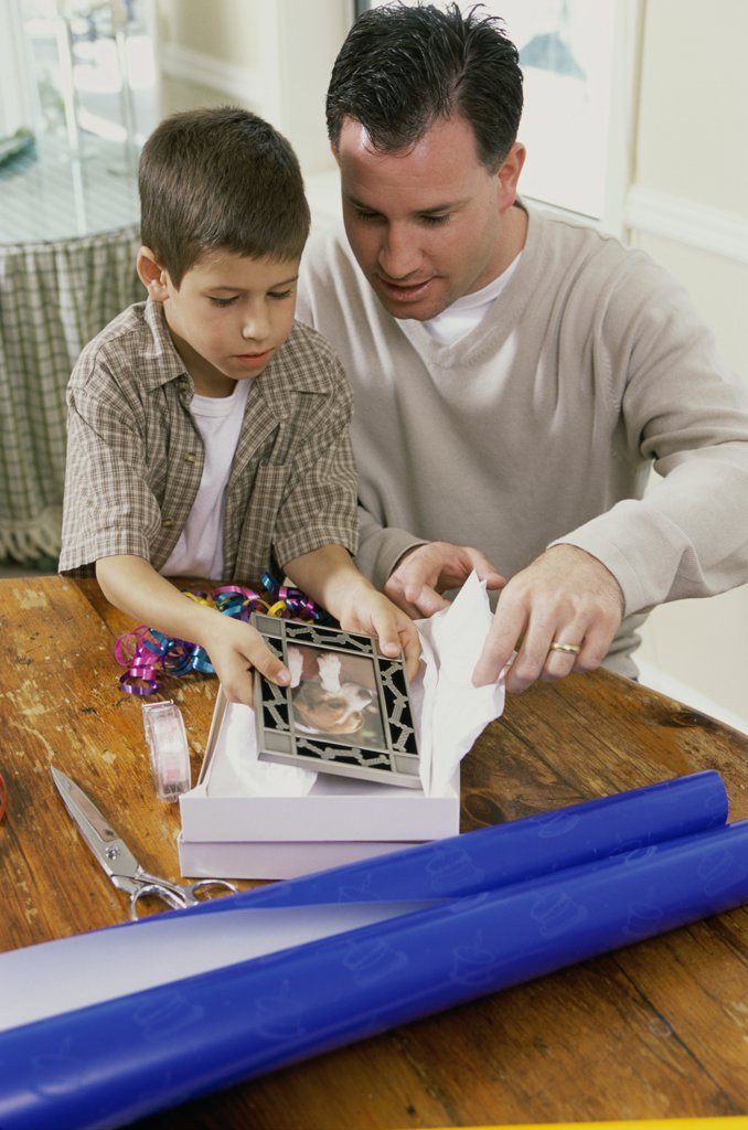 Stock Photo: 1574R-02359B Father and son wrapping a gift