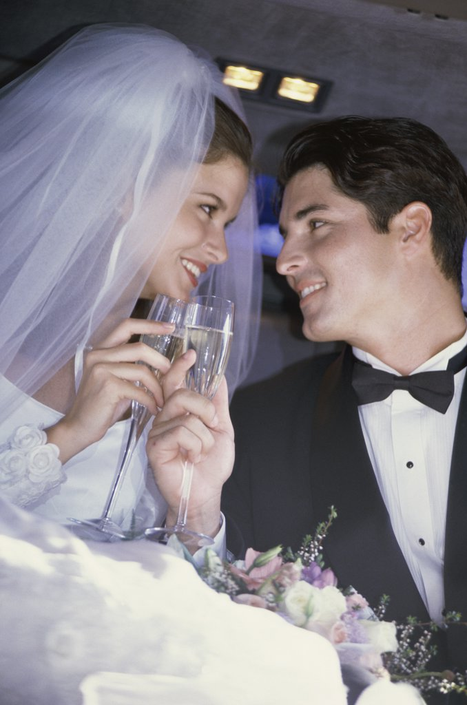 Newlywed couple toasting with champagne glasses in a car : Stock Photo