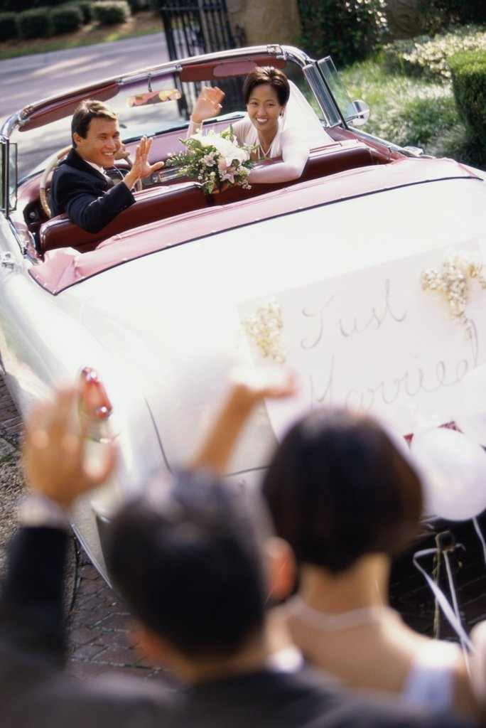 High angle view of a newlywed couple waving from a convertible car : Stock Photo