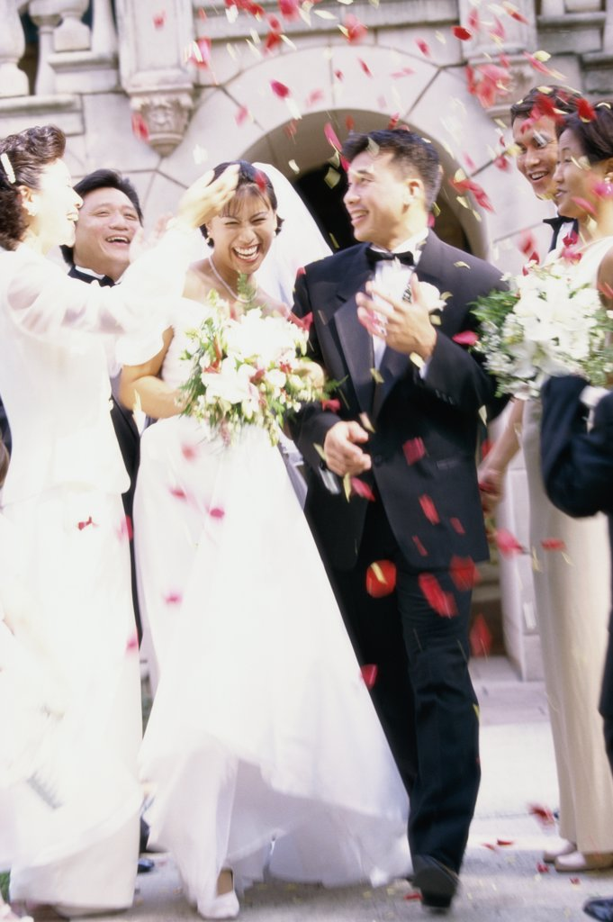 Flower petals being thrown on a bride and groom : Stock Photo