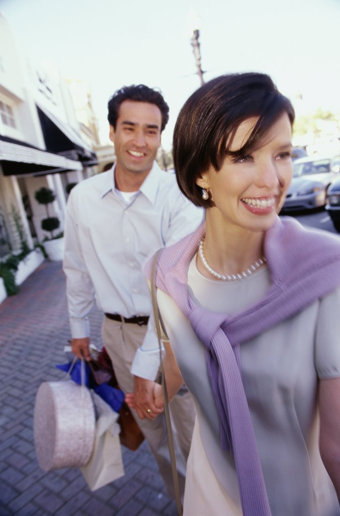 Mid adult couple carrying shopping bags : Stock Photo