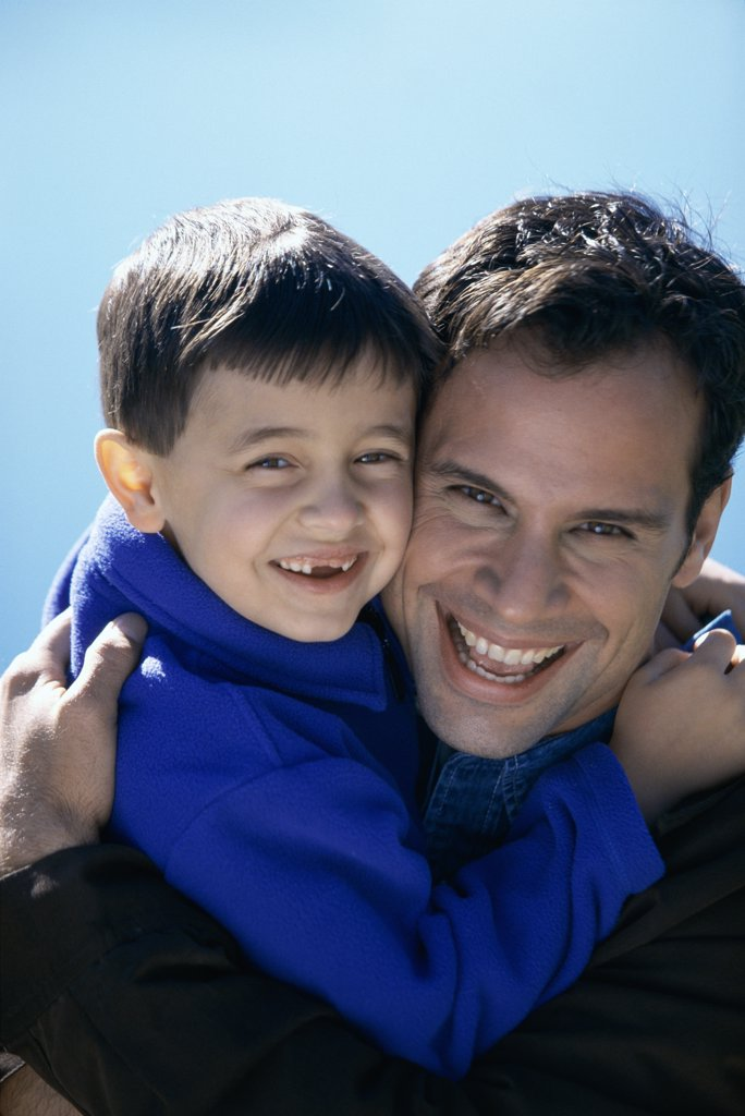 Close-up of a father hugging his son : Stock Photo