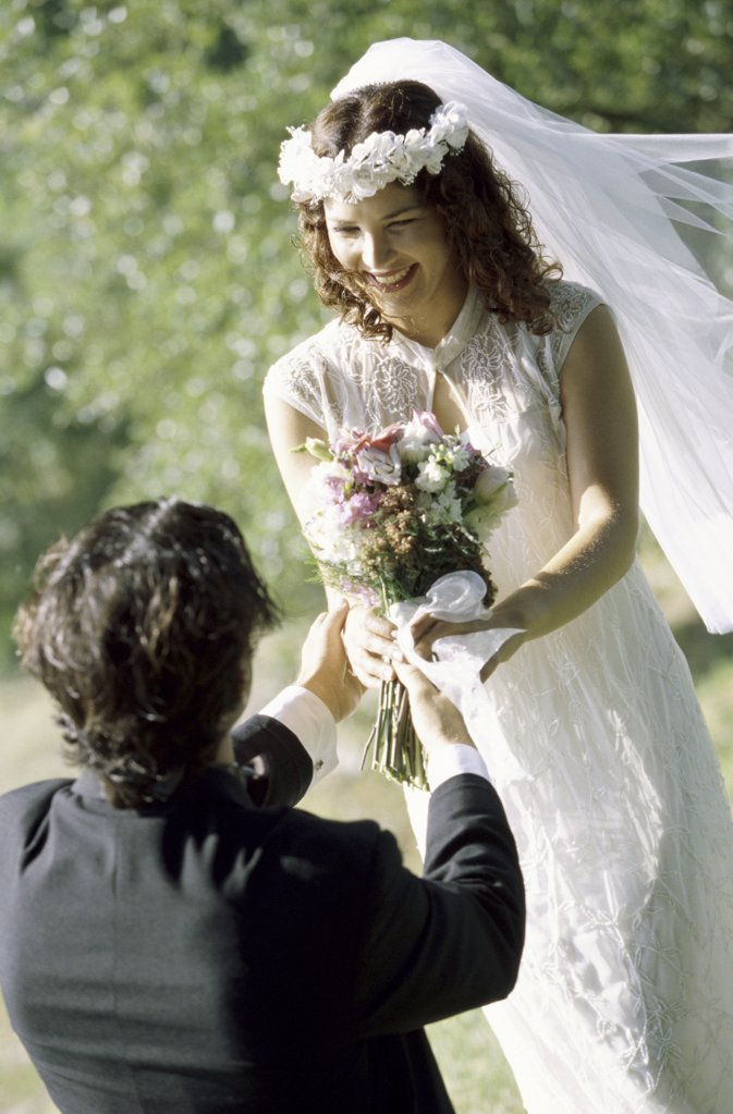 High angle view of a groom giving a bouquet of flowers to his bride : Stock Photo