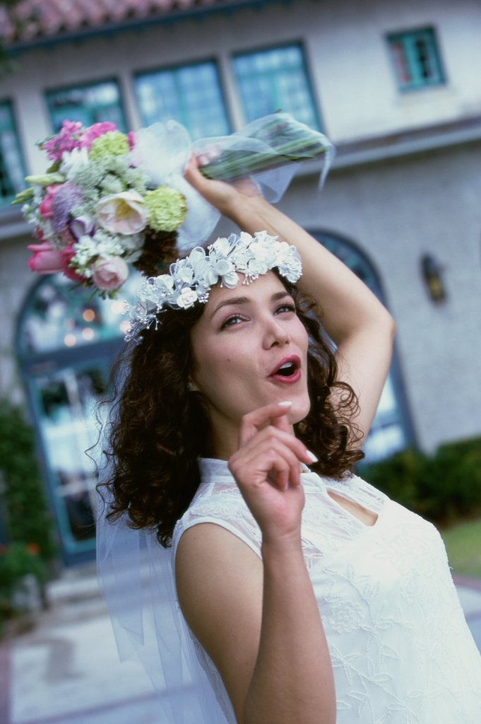 Newlywed young woman preparing to toss the bouquet : Stock Photo