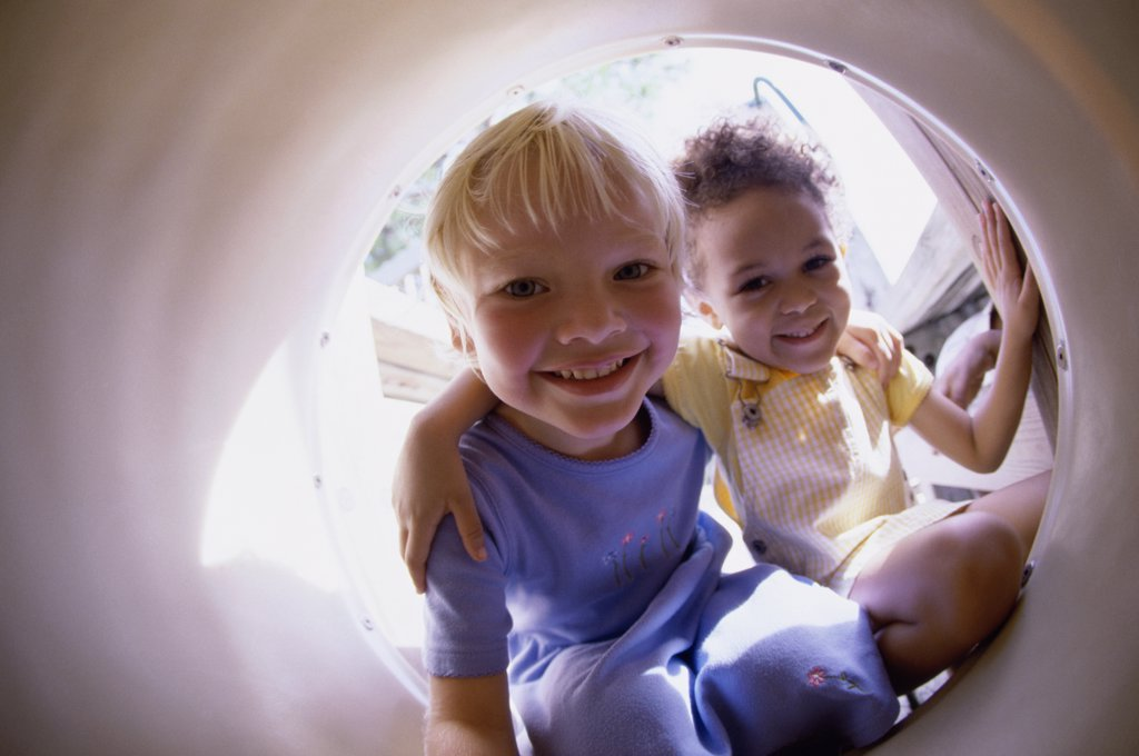 Portrait of two girls sitting in a tube : Stock Photo