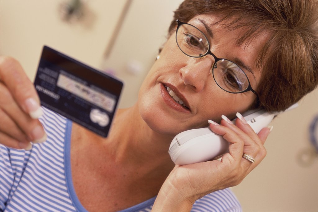 Mid adult woman talking on a cordless phone holding a credit card : Stock Photo