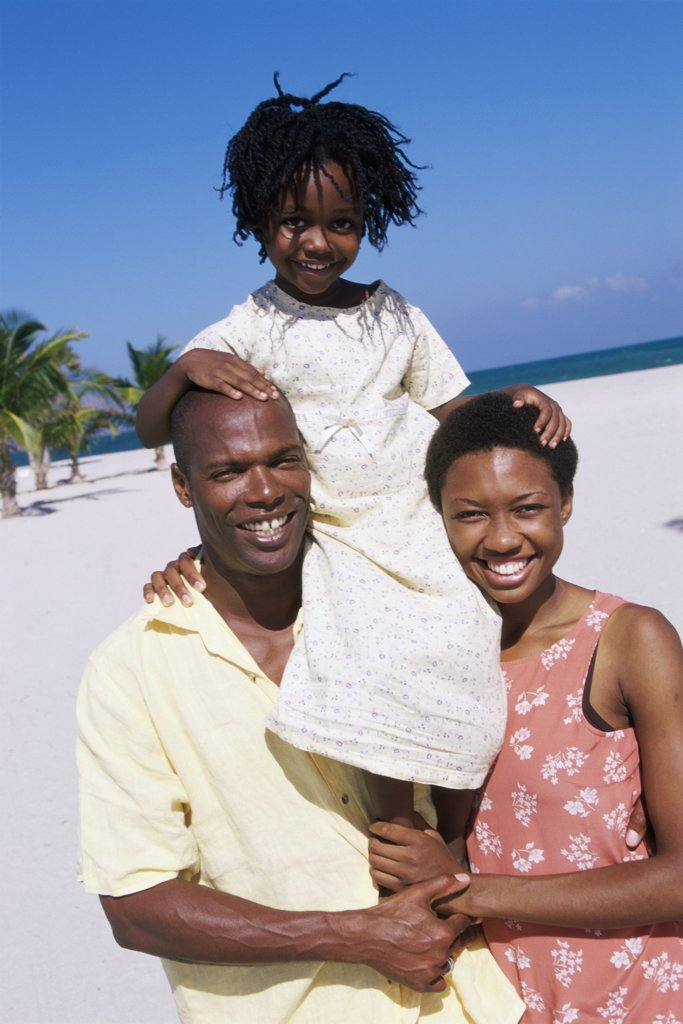 Portrait of parents carrying their daughter on their shoulders : Stock Photo