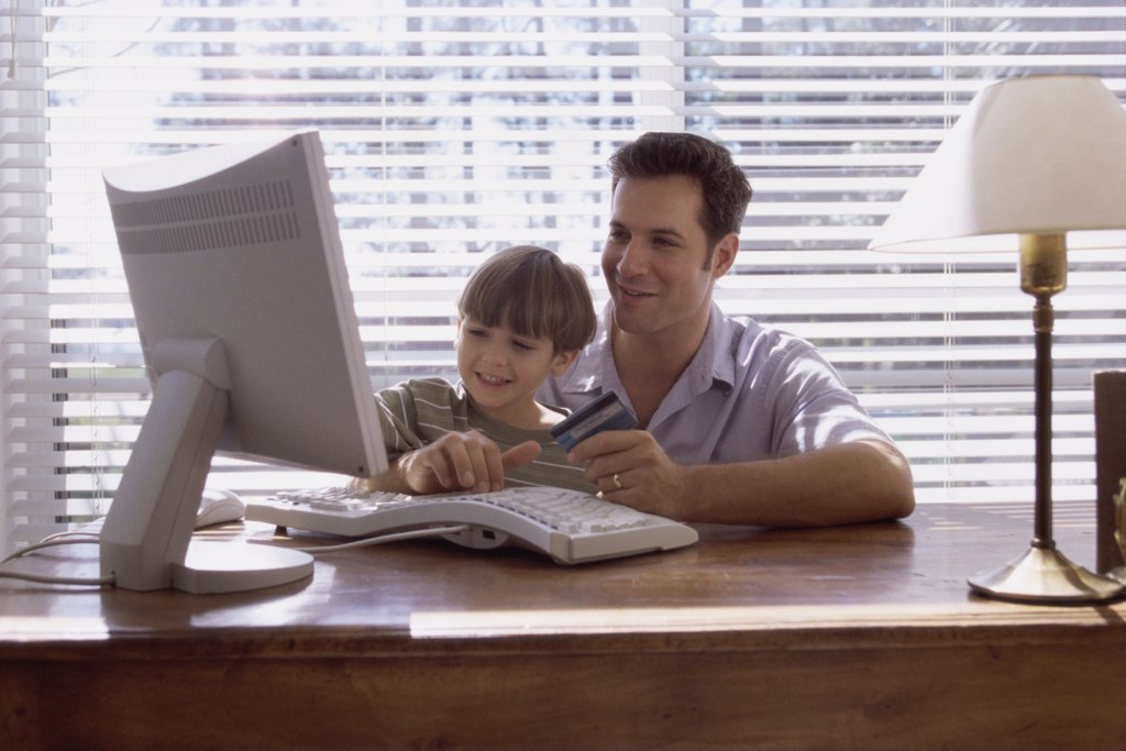 Father and his son sitting in front of a computer : Stock Photo