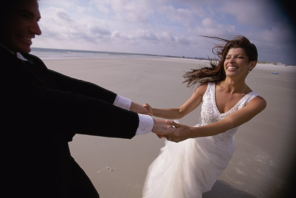 Stock Photo: 1574R-02688C Newlywed couple spinning each other on the beach