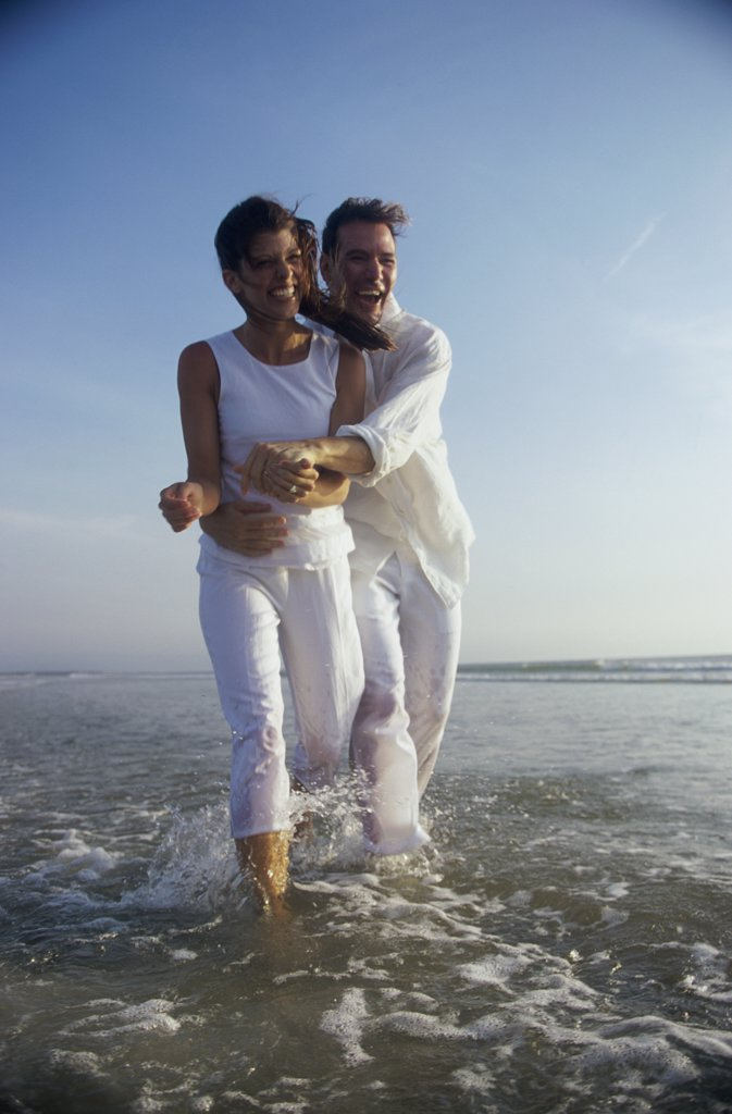 Young couple holding each other on the beach : Stock Photo