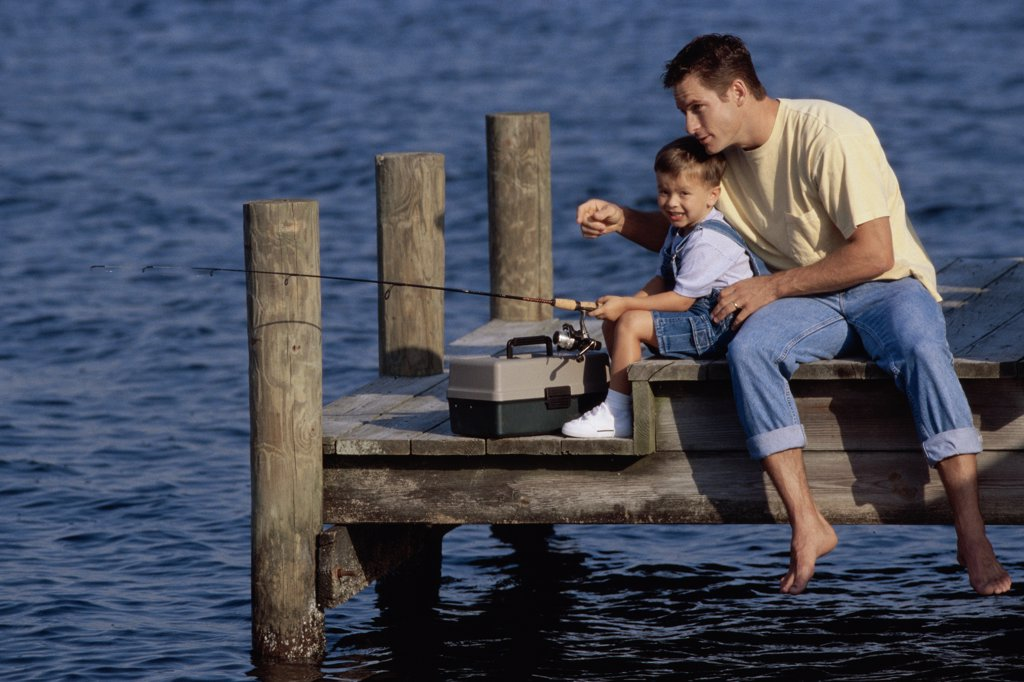 Stock Photo: 1574R-02703B Father and his son sitting on a pier fishing