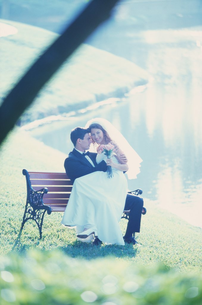 Stock Photo: 1574R-02733C Newlywed couple sitting on a park bench