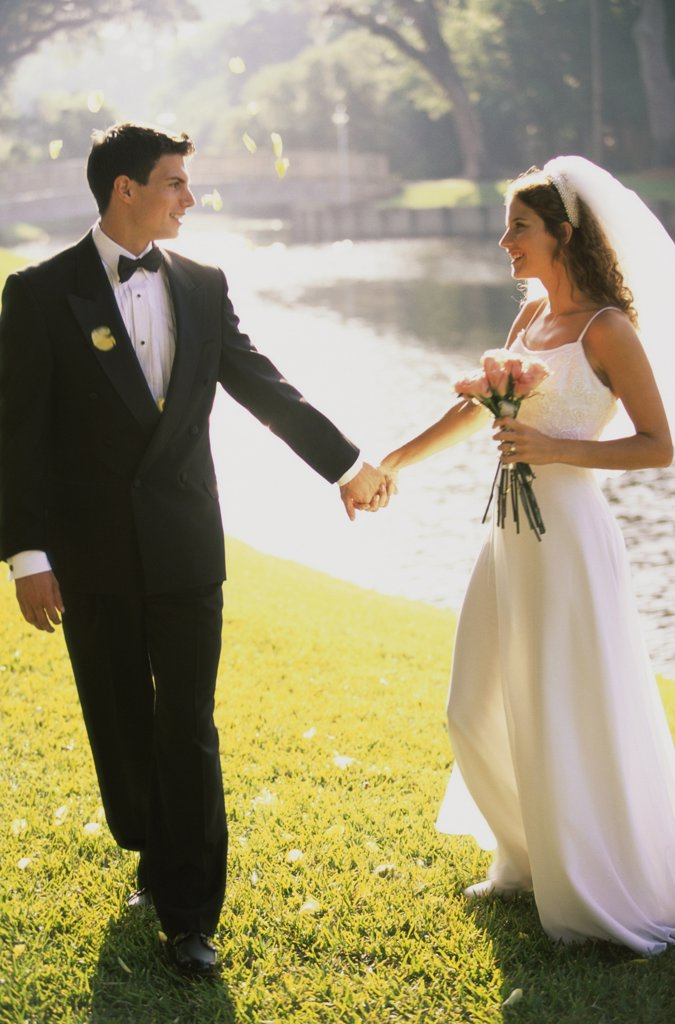 Newlywed couple holding hands and walking by a lake : Stock Photo