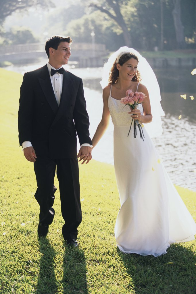 Stock Photo: 1574R-02734D Newlywed couple holding hands and walking by a lake