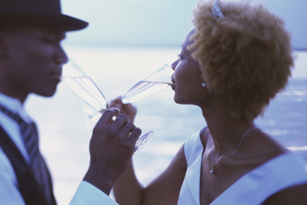 Stock Photo: 1574R-02745A Side profile of a newlywed couple drinking champagne on the beach