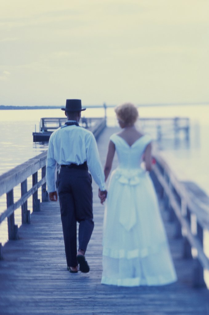Newlywed couple walking on a pier : Stock Photo
