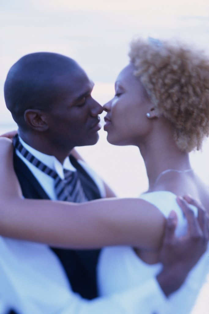 Stock Photo: 1574R-02753B Newlywed couple kissing each other