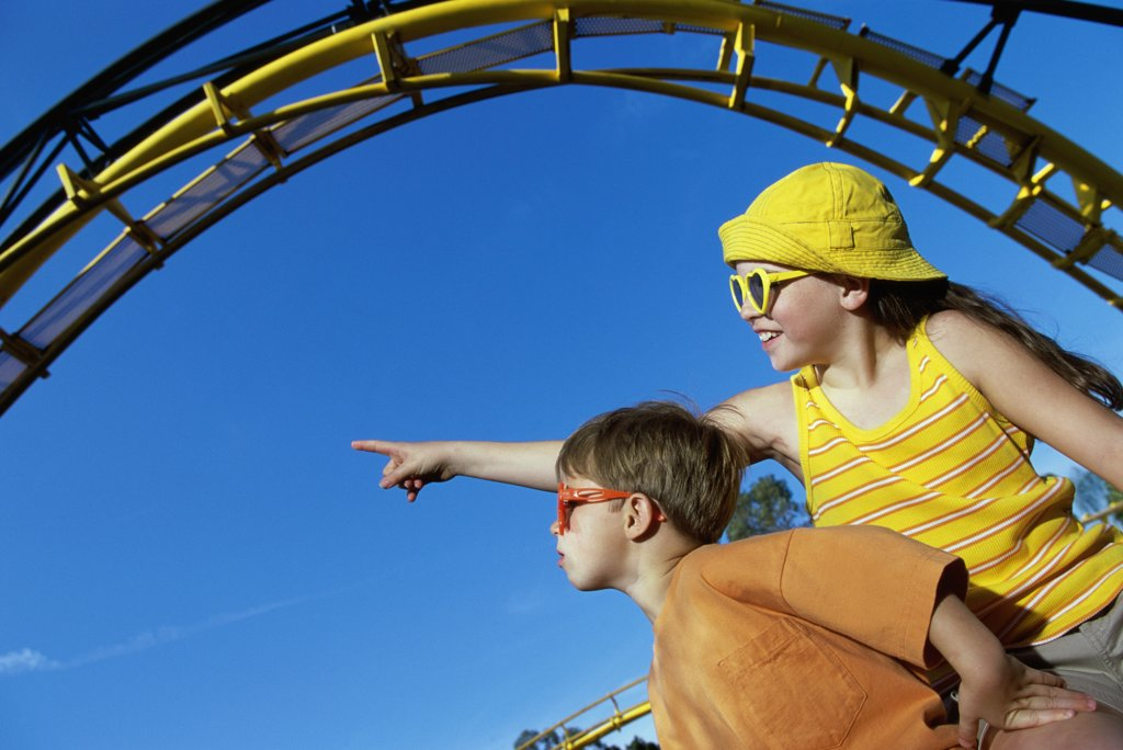 Low angle view of a boy and a girl in an amusement park : Stock Photo