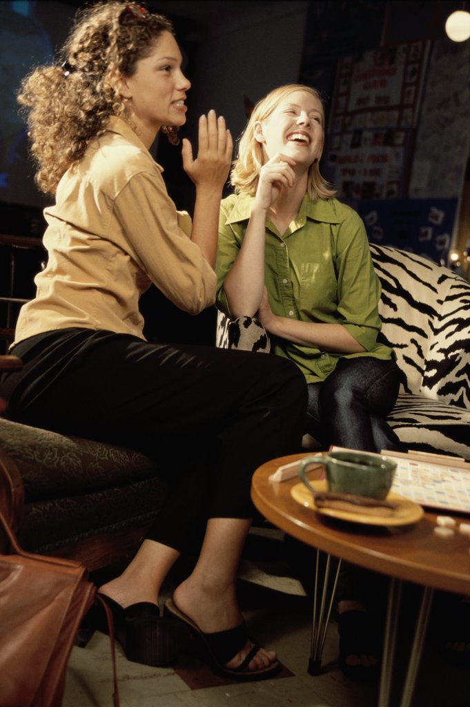 Two young women sitting in a cafeteria whispering : Stock Photo