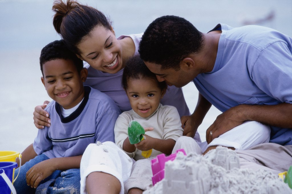 Parents with their son and daughter on the beach : Stock Photo