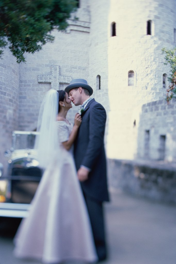 Stock Photo: 1574R-03050B Newlywed couple kissing each other in front of an antique car