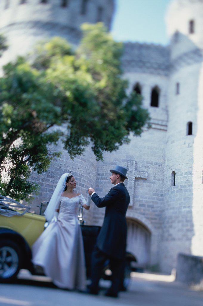 Stock Photo: 1574R-03053E Groom helping his bride into an antique car