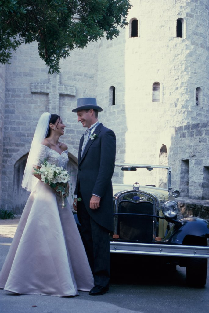 Stock Photo: 1574R-03054A Newlywed couple standing in front of an antique car