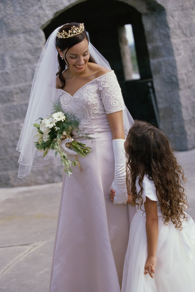 Bride holding a bouquet of flowers talking to a flower girl : Stock Photo