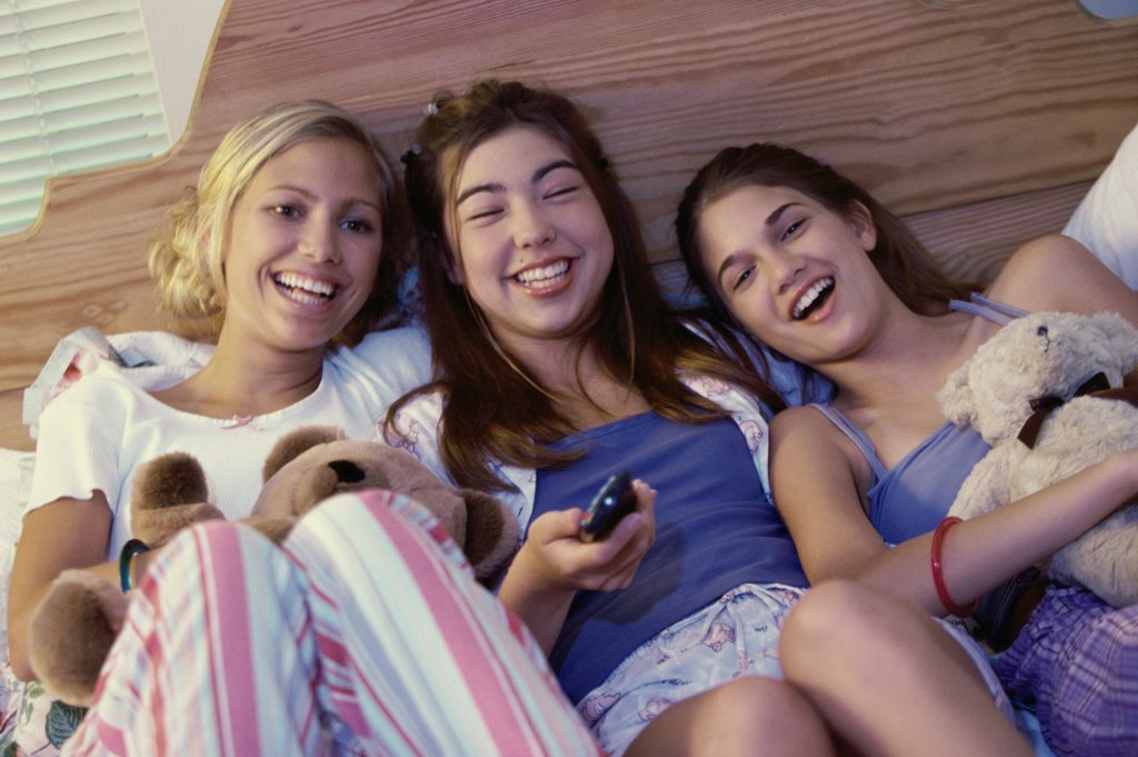 Three teenage girls lying on a bed watching television : Stock Photo