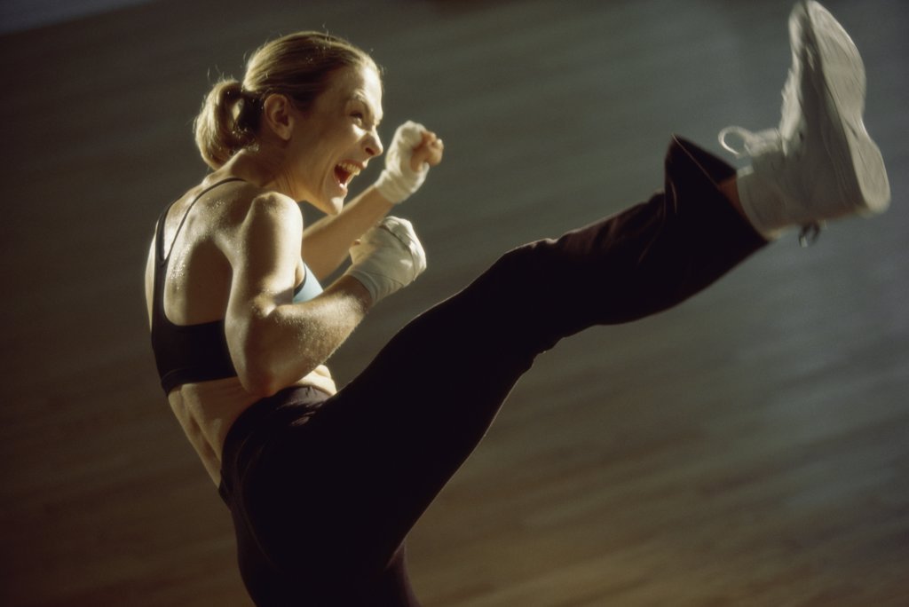 Side profile of a young woman kickboxing : Stock Photo